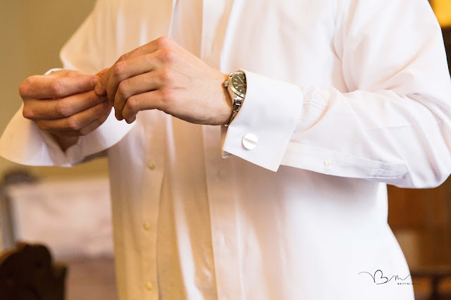 Groom putting on cuff links