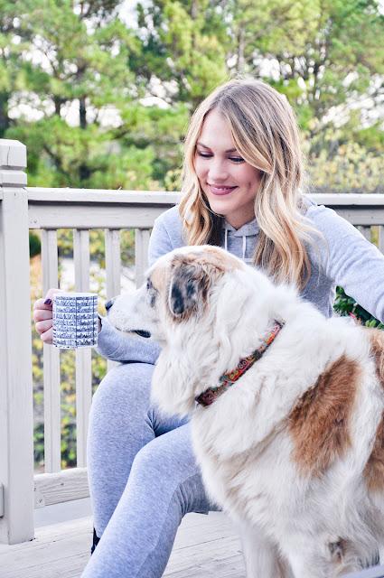 girl and dog sniffing coffee mug