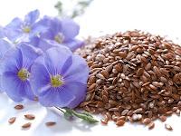 Keten tohumları ve yanındaki mor çiçekli bitkisi