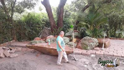 Execução do calçamento com pedra folheta com os redondos de paralelepípedo nos pés das árvores com colocação do banco de pedra natural com a execução do canteiro com pedra no jardim em residência em Itatiba-SP.