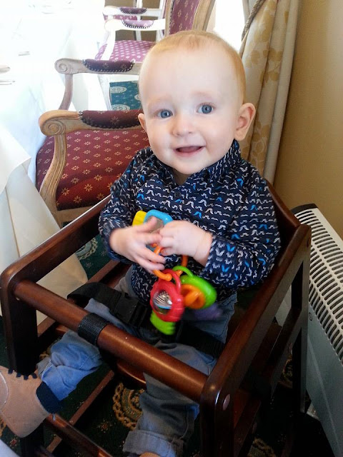 Smartly dressed toddler sitting in a highchair in posh surroundings