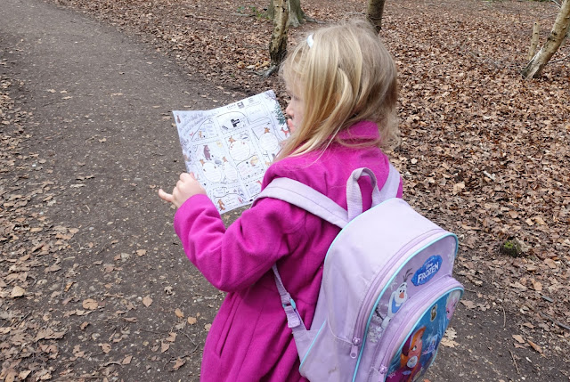 A girl in a pink coat looking at a hand drawn map in a forest