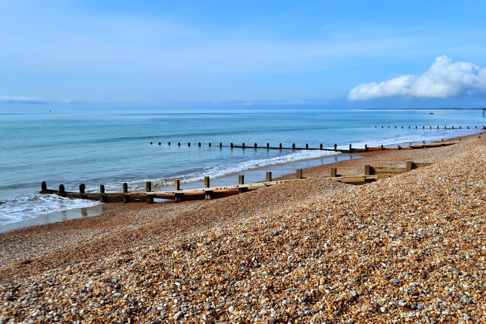 a sloping shingle beach leads into a beautiful blue sea