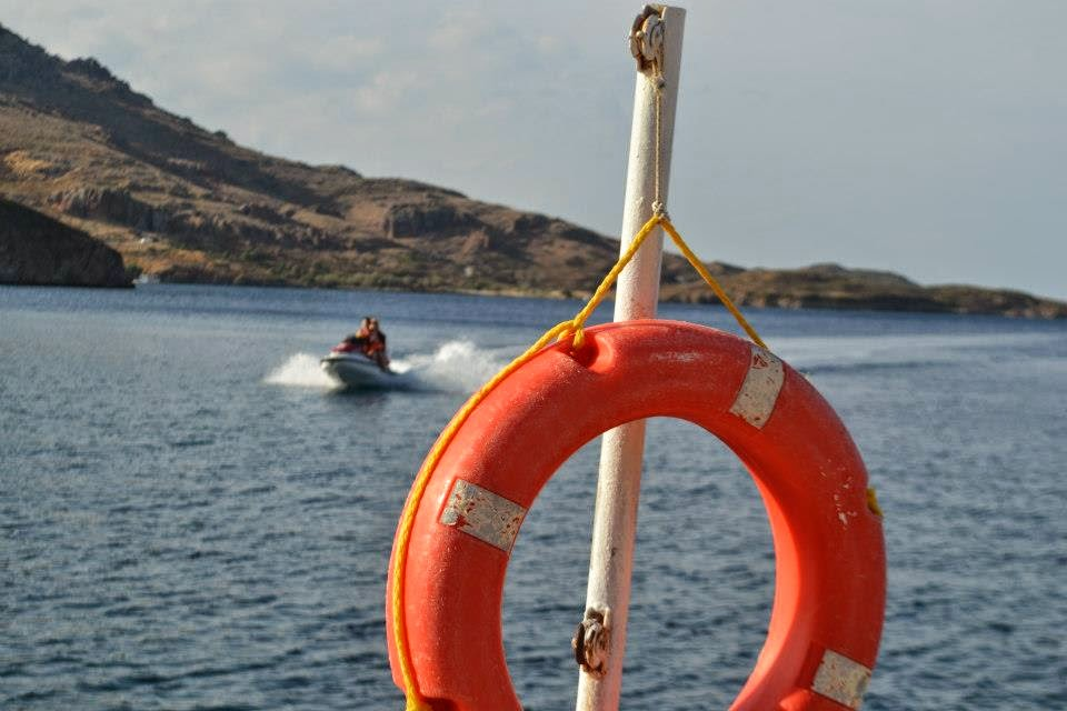 Photograph of a life vest with the ocean in the background. a jet ski can be seen splashing about to the side of the life vest