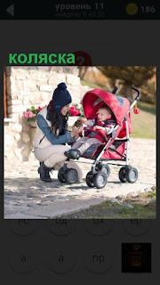 стоит коляска с ребенком и рядом мама находится