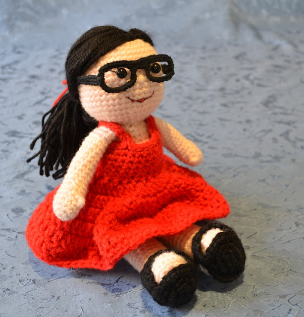 Kwokkie Doll in her very first outfit –a red summer dress with black sandals, black glasses and a red ribbon to tie her long black straight hair into a low ponytail.