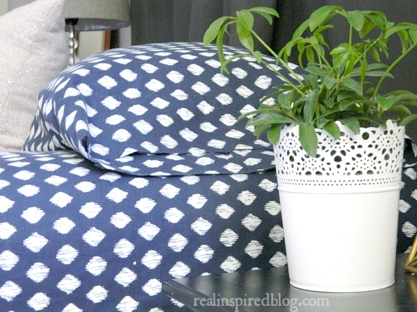 navy blue ikat cotton sheets on bed with green plant