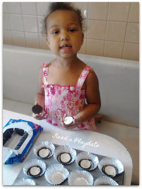 Little helper pulling apart cookies for cupcakes.