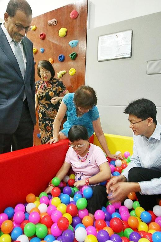 Ms Xue Er (in pink) playing in the ball pit, with UAE Ambassador to Singapore Mohamed Omar Abdulla Balfaqeeh (far left), Central Singapore District Mayor Denise Phua (in blue) and Minds Board honorary assistant secretary Daniel Tan (right).