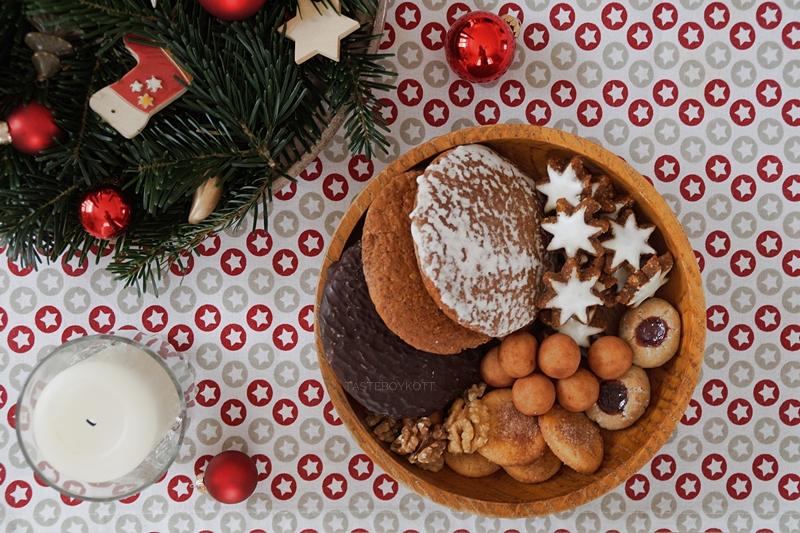 Traditionell-moderne Weihnachtsdeko mit roten Akzenten: Holzschale mit Plätzchen, Adventskranz mit Tanne und Tischläufer mit Sternen.