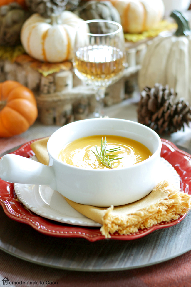 butternut squash soup served on French onion soup bowls as part of a Fall tablescape with red plates, yellow napkins and lots of pumpkins