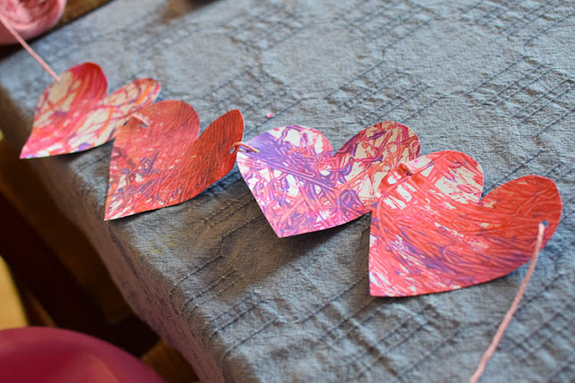 Valentine's Day Marble Painted Hearts and Valentine Garland- fun and easy painting process art activity for Valentine's Day. Great for preschool, kindergarten, or elementary kids. Leave as is or string into a pretty garland for decoration!