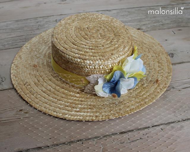 Sombrero de paja con flores para boda sobre suelo de madera.