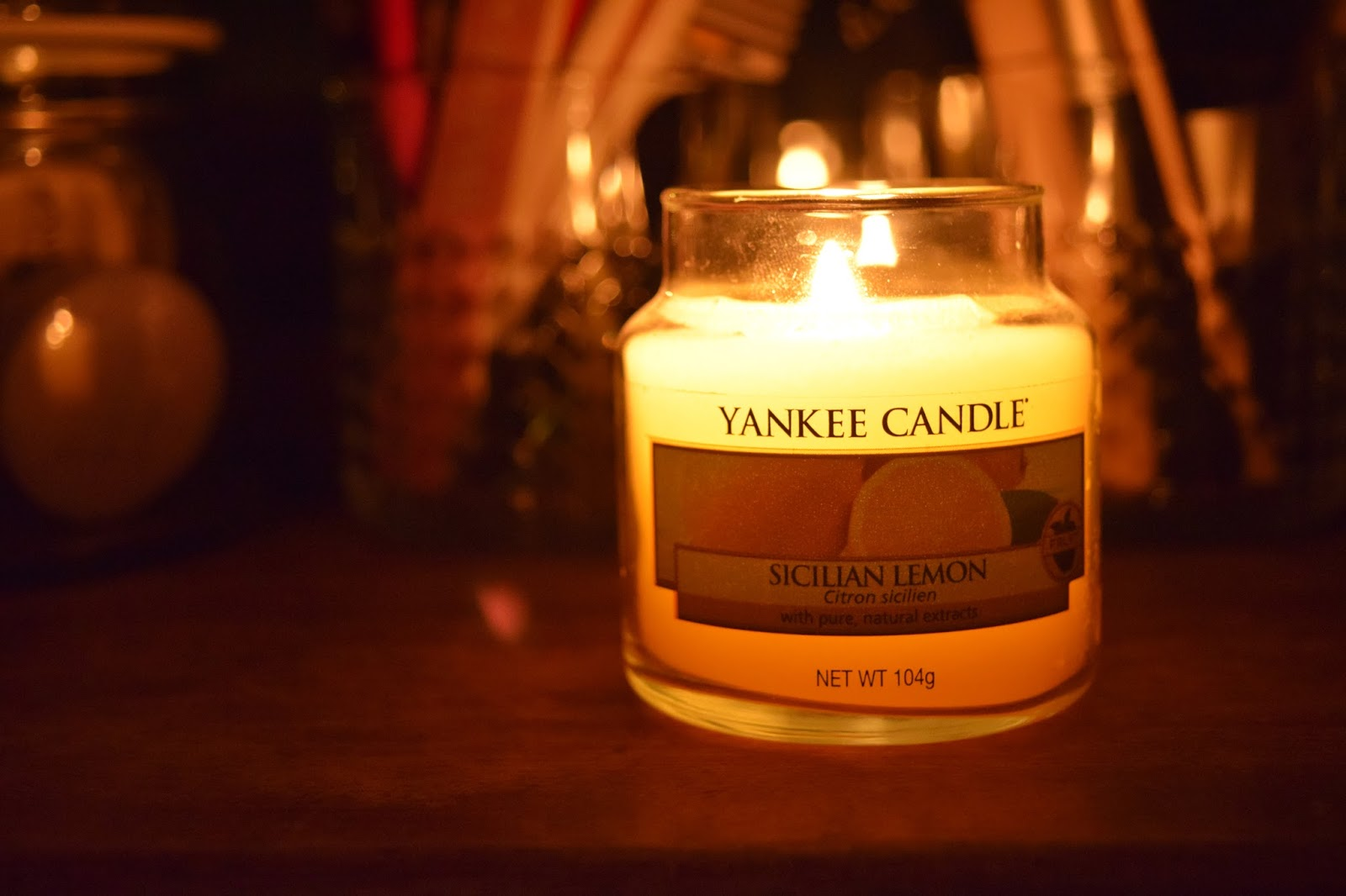 yellow yankee candle alight in a jar