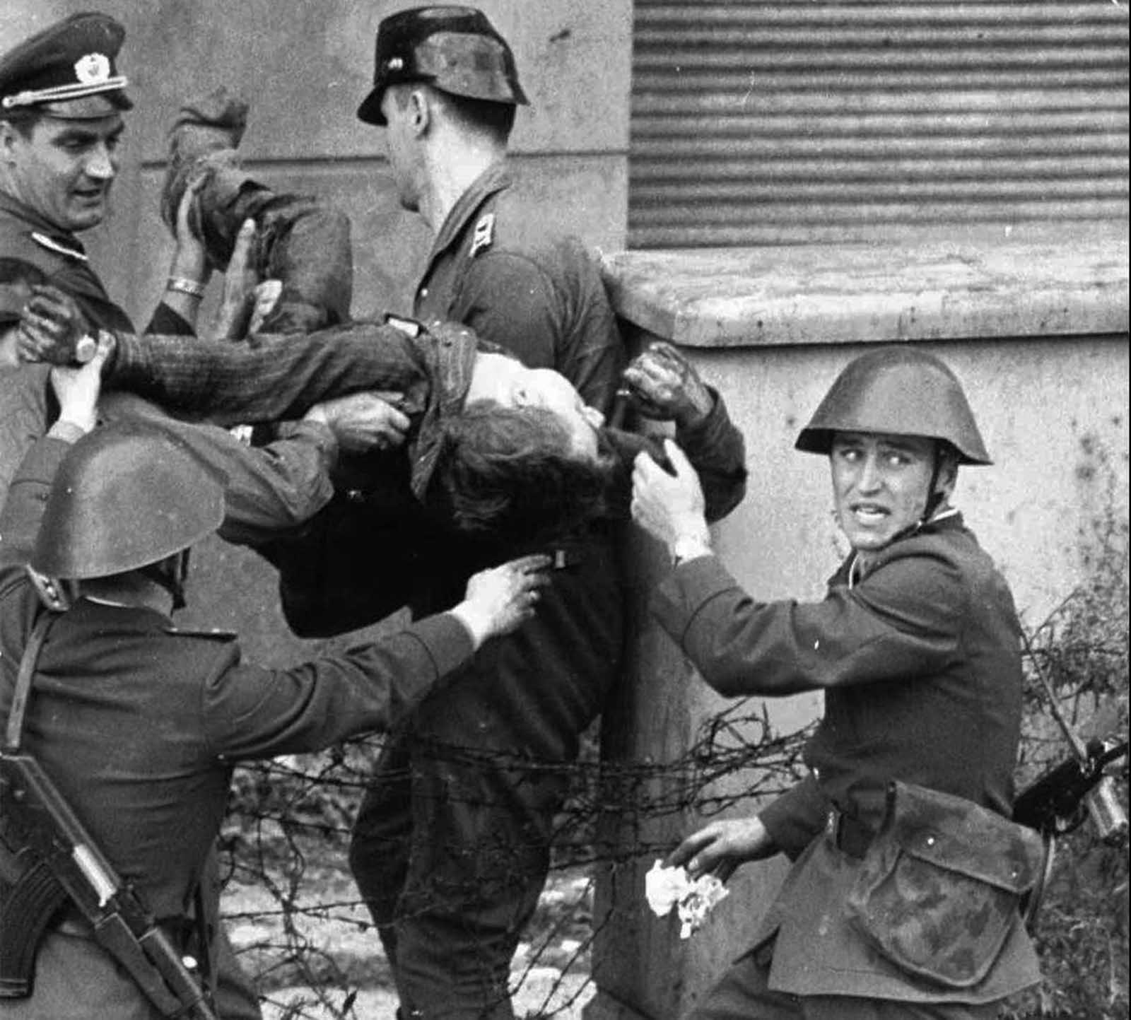 Dying Peter Fechter is carried away by East German border guards who shot him down when he tried to flee to the west in this August 17, 1962 photo. Fechter was lying 50 minutes in no-man's land before he was taken to a hospital where he died shortly after arrival.