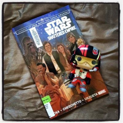 A trade paperback copy of Shattered Empire rests on a bronze comforter. Its cover features a painting of the Star Wars cast: Chewie, Lando, Wicket, Han, Leia, Luke, Artoo, and Threepio. A Funko bobblehead of Poe Dameron in his orange flight suit and black helmet rests across the book.