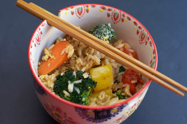 The finished bowl of rice with chop sticks on top of it.