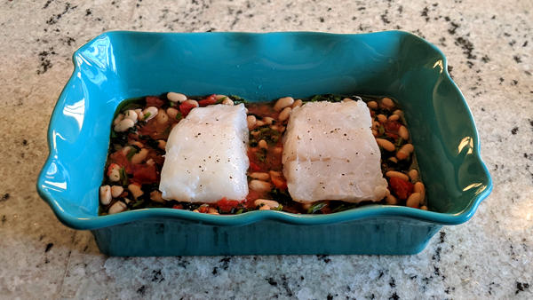 image of fish atop vegetables in casserole dish, ready to go into the oven