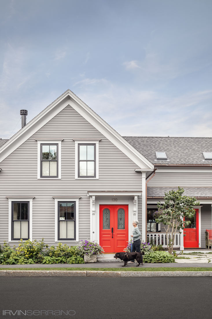 A woman walks her dog in front of a renovated home with a red door on Peaks Island in coastal Maine.