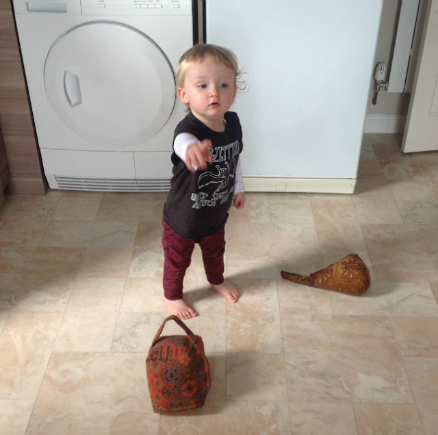 toddler stood in kitchen with two doorstops pointing