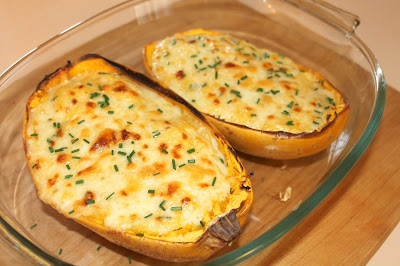Two spaghetti squash halves baked with cheesey spaghetti squash inside.