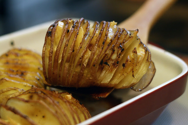 A square dish with a Hasselback Potato stuffed with brie cheese being lifted out.