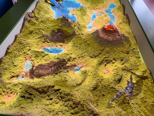A sand pit that shows mountains and lakes and dinosaurs