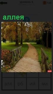 Через мостик ведет тропинка на аллею дальше в красивый парк осенью