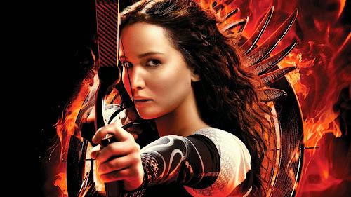 Jennifer Lawrence faz pose como Kaniss Everdeen e seu arco-e-flecha no filme sensação Jogos Vorazes