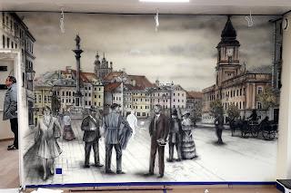 Malowanie graffiti na ścianie w salonie, obraz namalowany na scianie przedstawia Plac Zamkowy w Warszawie