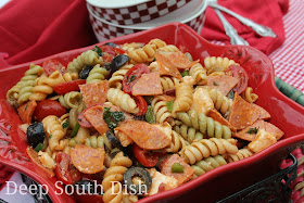 ri-color rotini pasta is paired with some of my favorite pizza toppings, purple onion, green and red bell pepper, black olives, pepperoni, bacon, mushrooms, grape tomatoes and mozzarella and dressed with a spicy tomato dressing.