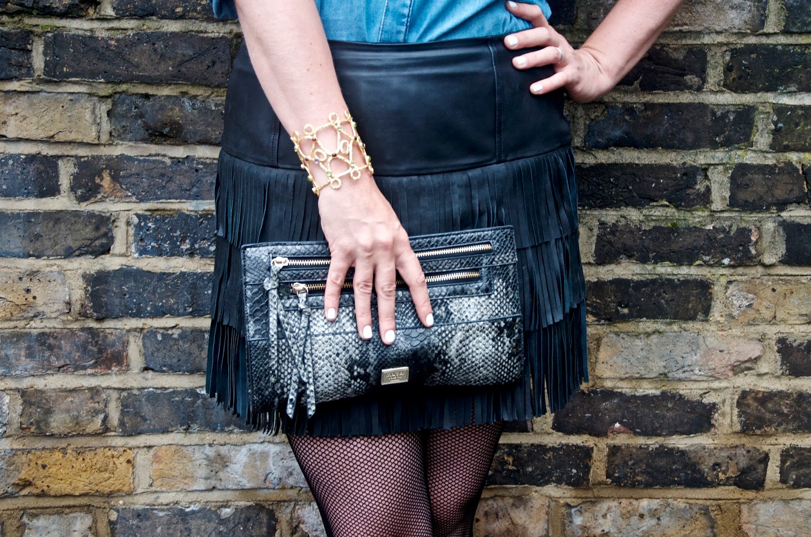 snakeskin clutch, gold cuff, denim shirt, leather fringe skirt and black fishnet tights
