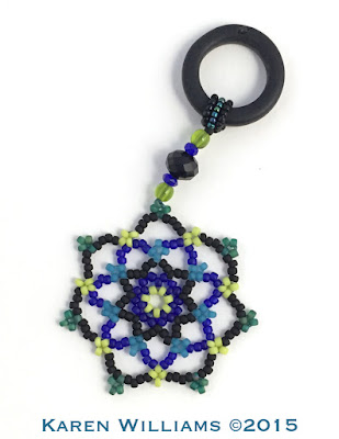 Summer beaded Snowflake Mandalas in turquoise, teal, black and lime green.  Pendant with sea glass ring by artist Karen Williams