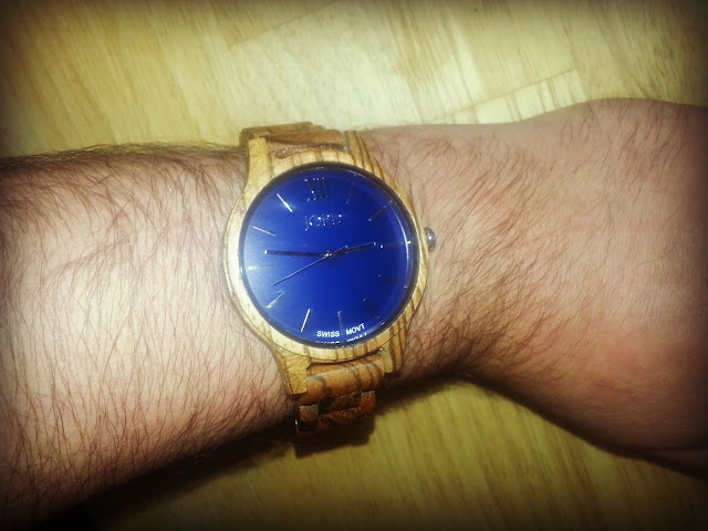 Man's wrist modelling Jord wood watch with navy blue face.