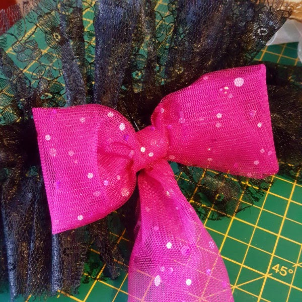 sparkling pink tulle made into a bow shape pinned to black lace