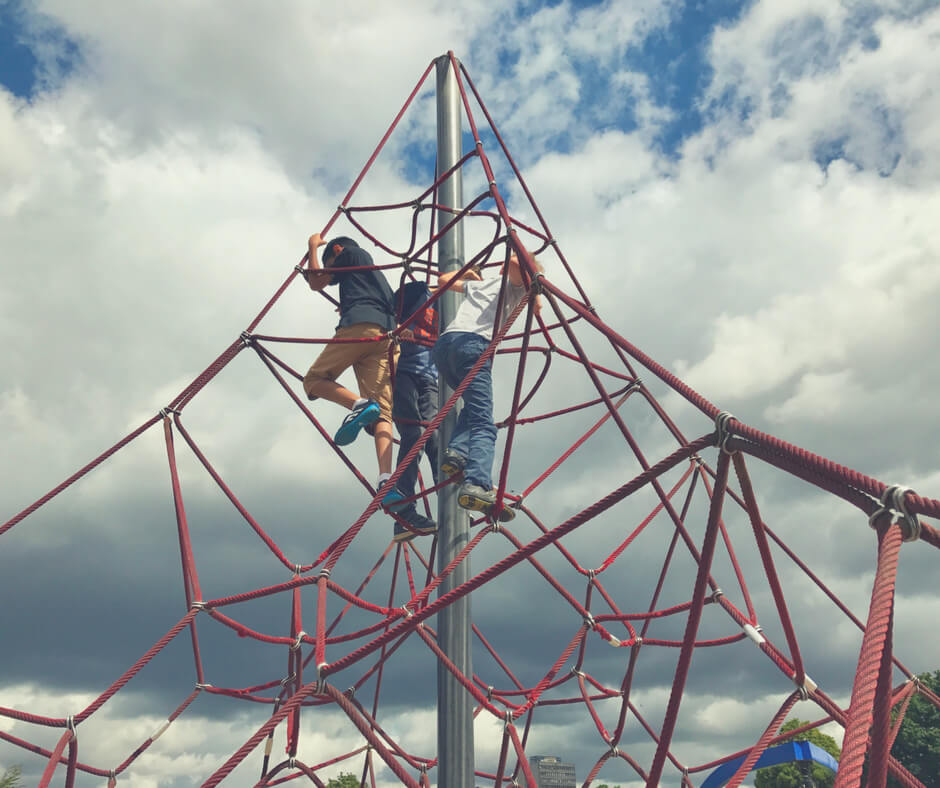 Three boys climb to the top of a climbing frame. The sky is cloudy behind them.