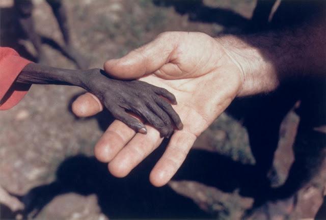 Czarna dłoń wygłodzonego dziecka w dłoni mnicha, który pomagał ofiarom klęski.