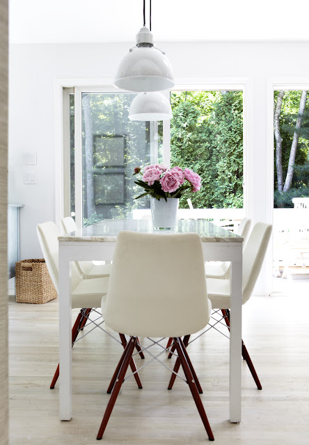 Dining room with white table with a marble top holding a vase of pink flowers surrounded by white chairs with wooden legs overlooking a lush garden