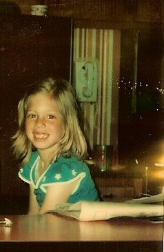 Exquisitely Unremarkable Author as a young girl sitting in the kitchen