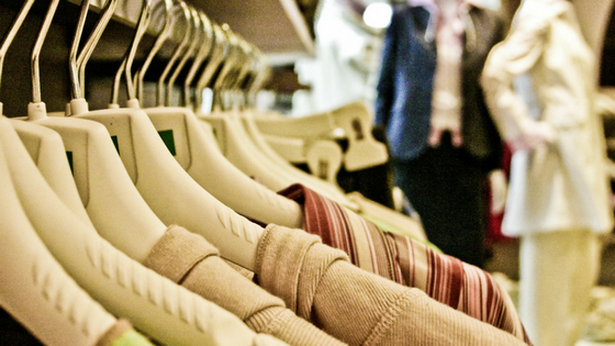 A slelection of beige/nude clothing hanging on a rail.