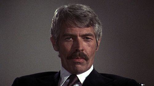James Coburn wearing a suit and tie in The Internecine Project