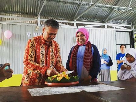 Kepala Diskominfotik Provinsi Bengkulu, Edi Prawisnu memotong puncak tumpeng dan diserahkan kepada Ketua Bobe, Mildaini. Foto: Prio jalanjalankitadotcom.