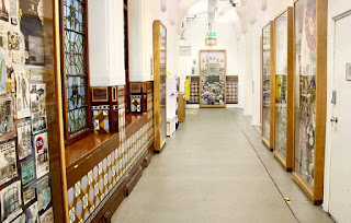 A long corridor with a bright light above with white walls covered in colourful tapestry on a bright background.