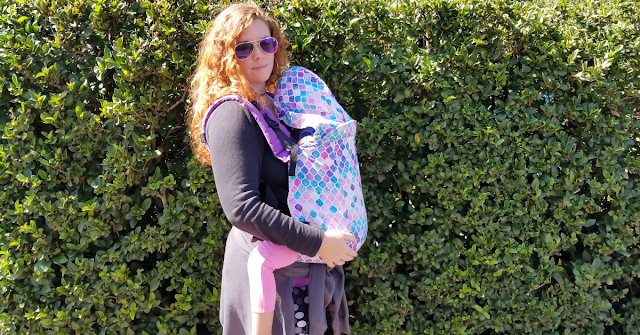 Curly red haired woman standing in front of green bushes,wearing a black sweater and sunglasses. She's babywearing her sleeping toddler in a soft structured carrier, a Kinderpack, that is purple, pink, and blue.
