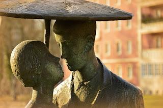 escultura de homem e mulher se olhando sob uma sombrinha