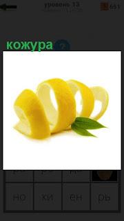 Лежит желтая кожура от лимона свернутая колечками и зеленый листок
