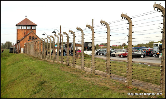 Barbed wire electric fences and guard towers in Auschwitz II (Birkenau).