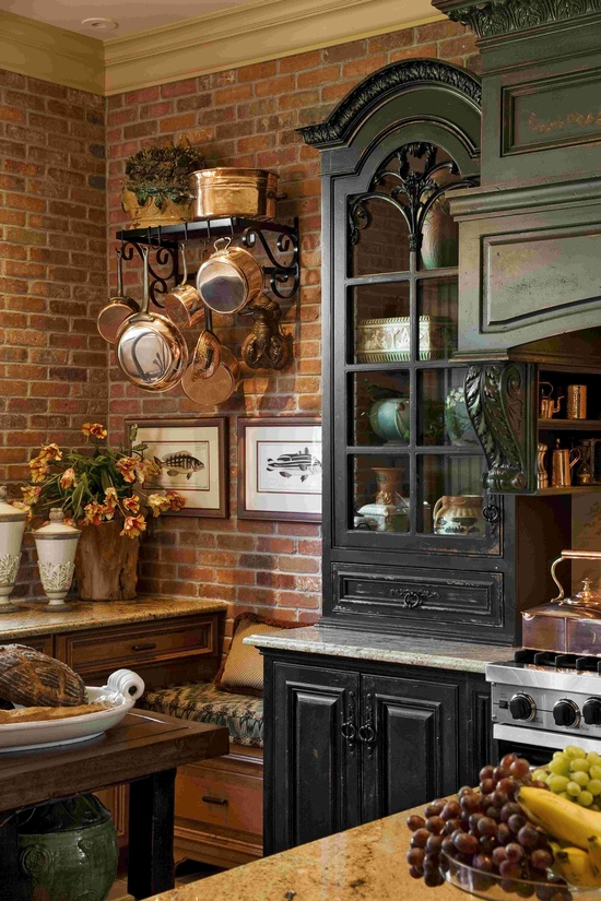 The dark brick walls and black painted cabinets look amazing in this elegant farmhouse kitchen