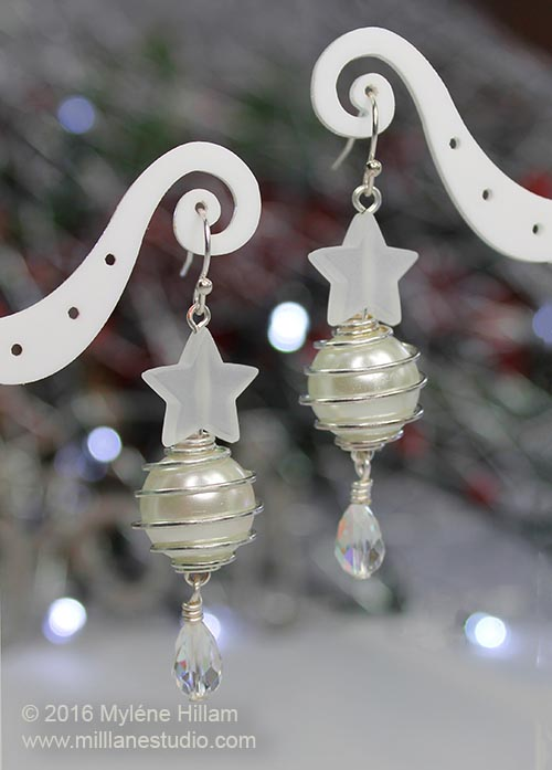 Snow white Christmas earrings with a faceted tear drop crystal dangling below and large white glass pearl in a wire cage, attached to a frosted white star.