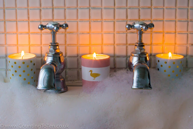 The Fuzzy Duck Pink Gin Fizz Trio Candle Set of two white candles with gold spots and a pink and white candle burning on the side of the bath with lots of bubbles